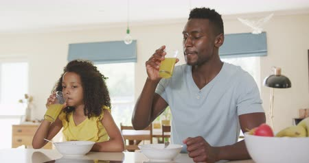 столовая : Front view of an African American man and his mixed race daughter enjoying time at home together, sitting by a table, eating breakfast, drinking juice, in slow motion
