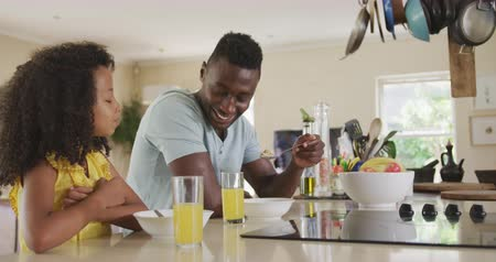 kahvaltı : Side view of an African American man and his mixed race daughter enjoying time at home together, sitting by a table, eating cereals for breakfast, in slow motion