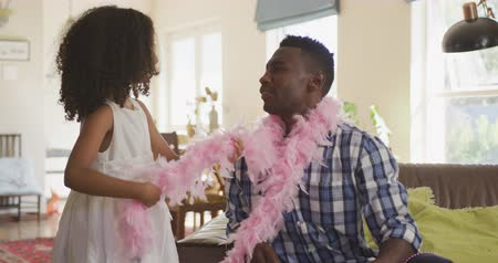 боа : Front view of an African American man and his mixed race daughter enjoying time at home together, a girl is putting a pink feather boa around her fathers neck, in slow motion Стоковые видеозаписи