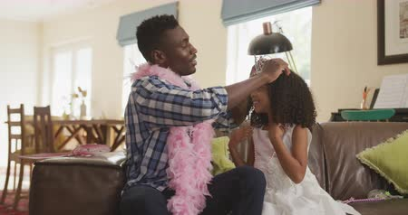 боа : Side view of an African American man and his mixed race daughter enjoying time at home together, a man wearing a pink boa is putting tiara on his daughters head, in slow motion