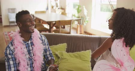боа : Front view of an African American man and his mixed race daughter enjoying time at home together, a girl dressed as a fairy is casting spells, waving her wand at her father, wearing a pink feather boa, in slow motion