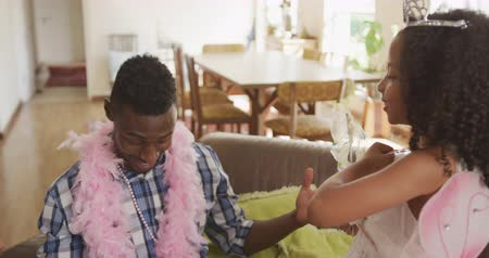 boa : Front view of an African American man and his mixed race daughter enjoying time at home together, a girl dressed as a fairy is casting spells, waving her wand at her father, wearing a pink feather boa, kissing him on the cheek, in slow motion Stock Footage