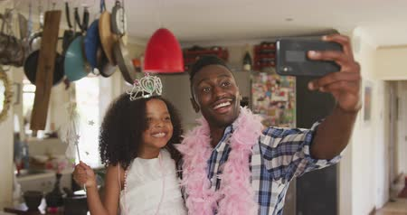 боа : Front view of an African American man and his mixed race daughter enjoying time at home together, a girl is dressed as a fairy and a man is wearing a pink feather boa, taking a selfie, a girl is kissing her father on a cheek, in slow motion