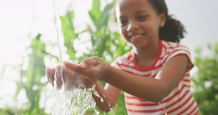 washing hands : Side view close up of a mixed race girl enjoying her time at the garden, washing her hands, in slow motion Stock Footage