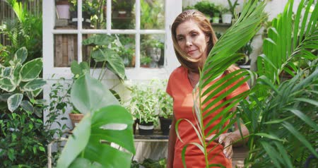 orange t shirt : Front view of a Caucasian woman with long brown hair, wearing an orange t shirt, enjoying time in a sunny garden, inspecting plants outside a greenhouse, in slow motion