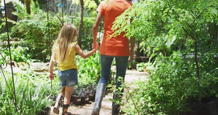 deneyim : Rear view of a Caucasian woman and her daughter enjoying time together in a sunny garden, holding hands and walking along a path between plants, in slow motion