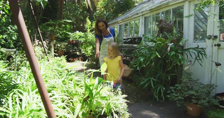söğüt : Front view of a Caucasian woman wearing an apron and her daughter enjoying time together in a sunny garden, looking at plants together and carrying baskets, in slow motion