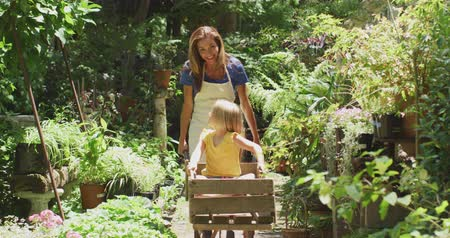 el arabası : Front view of a Caucasian woman wearing an apron and her daughter enjoying time in a sunny garden, the daughter sitting in a wheelbarrow while the mother pushes her along, looking at each other and smiling, in slow motion Stok Video