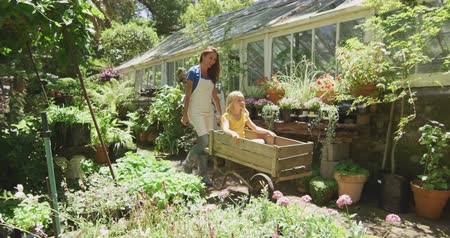 experiência : Side view of a Caucasian woman wearing an apron and her daughter enjoying time in a sunny garden, the daughter sitting in a wheelbarrow while the mother pushes her along, in slow motion