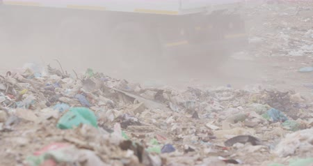 environmental awareness : Side view close up of truck driving accord rubbish piled on a landfill full of trash with vehicles working and clearing rubbish in the background in slow motion