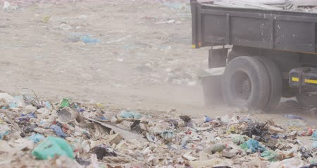 mensen massa : Side view close up of truck driving across rubbish piled on a landfill full of trash with vehicles working and clearing rubbish in the background in slow motion