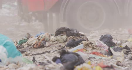 mensen massa : Close up of tyres of vehicle driving across rubbish piled on a landfill full of trash with vehicles working and clearing rubbish in the background in slow motion