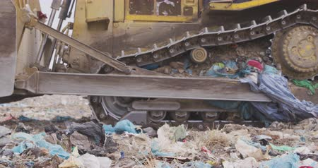 aquecimento global : Side view close up of vehicle working and clearing rubbish piled on a landfill full of trash with vehicles working and clearing rubbish in the background in slow motion