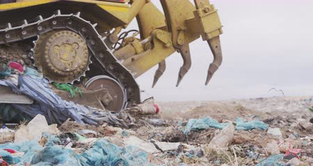 wysypisko śmieci : Side view close up of vehicle working and clearing rubbish piled on a landfill full of trash with vehicles working and clearing rubbish in the background in slow motion