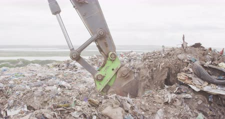 escavadora : Side view close up of digger working and clearing rubbish piled on a landfill full of trash with vehicles working and clearing rubbish in the background in slow motion