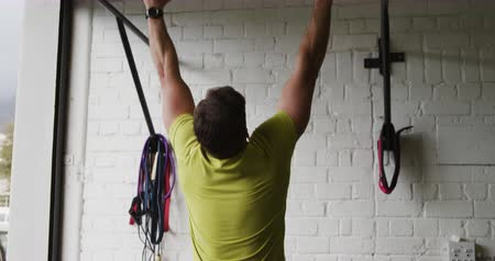 flexibilidade : Rear view of an athletic Caucasian man wearing sports clothes cross training at a gym, doing chin ups on a bar, then sitting down for a rest and rubbing his hands Stock Footage