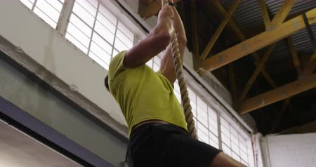 lano : Low angle view of an athletic Caucasian man wearing sports clothes cross training at a gym, climbing up a rope hanging from the ceiling