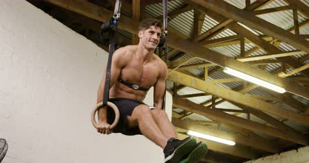 flexibilidade : Front view of a shirtless athletic Caucasian man wearing a chest strap heart rate monitor cross training at a gym, lifting himself up on gymnastic rings