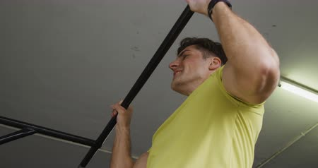 contra : Side view close up of an athletic Caucasian man wearing sports clothes cross training at a gym, doing chin ups holding onto a bar Stock Footage