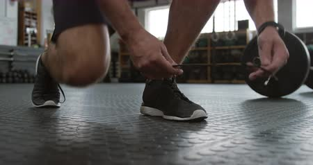 fonctionnel : Front view low section of an athletic Caucasian man wearing sports clothes and sports shoes cross training at a gym, kneeling and tying his shoelaces before weight training with barbells, on the floor beside him Vidéos Libres De Droits