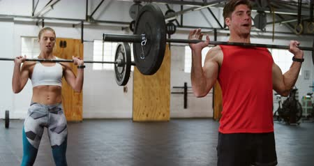 flexibilidade : Front view of an athletic Caucasian man and woman wearing sports clothes cross training at a gym, standing and weight training with barbells, lifting them from the floor and raising them from chest level above their heads