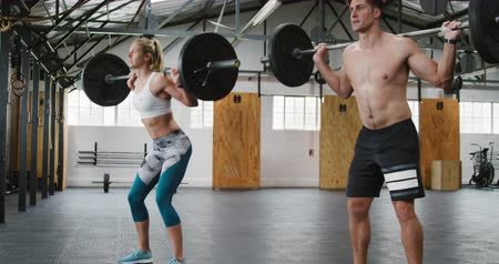 souplesse : Side view of an athletic Caucasian man and woman wearing sports clothes cross training at a gym, standing and weight training with barbells, squatting down and rising holding the barbells on their shoulders, the man is shirtless Vidéos Libres De Droits