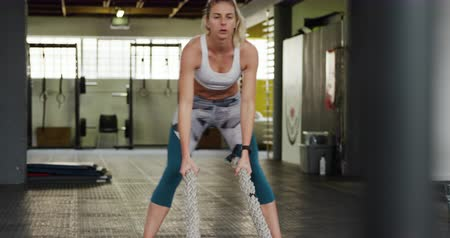 flexibilidade : Front view of an athletic Caucasian woman wearing sports clothes cross training at a gym, working out with battle ropes Stock Footage