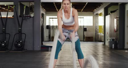 souplesse : Front view of an athletic Caucasian woman wearing sports clothes cross training at a gym, working out with battle ropes Vidéos Libres De Droits