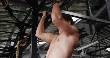 contra : Side view close up of a shirtless athletic Caucasian man cross training at a gym, doing chin ups holding onto a bar Stock Footage