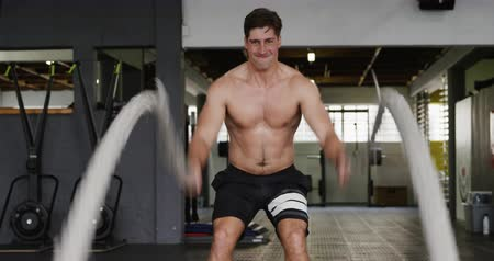 flexibilidade : Front view of a shirtless, athletic Caucasian man wearing sports clothes cross training at a gym, working out with battle ropes Stock Footage