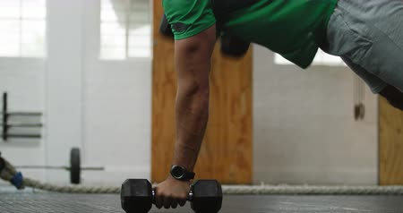 flexibilidade : Side view close up of an athletic Caucasian man wearing sports clothes cross training at a gym, weight training with dumbbells, lying in a press up position holding the dumbbells, and lifting alternate weights Stock Footage