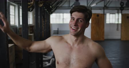 funcional : Portrait of a happy shirtless, handsome, athletic Caucasian man cross training at a gym, taking a break, looking to camera and smiling