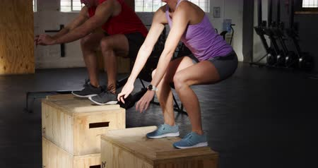 souplesse : Side view of an athletic Caucasian man and woman wearing sports clothes cross training at a gym, jumping onto boxes and landing with bent knees and arms outstretched in front of them, looking straight ahead, in slow motion