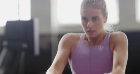 pull out : Front view close up of an athletic Caucasian woman wearing sports clothes cross training at a gym, sitting and exercising on a rowing machine, in slow motion