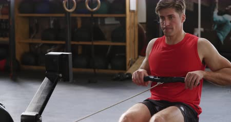 kürek çekme : Front view of an athletic Caucasian man wearing sports clothes cross training at a gym, sitting and exercising on a rowing machine, in slow motion