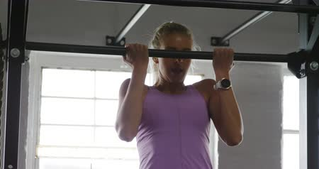 ハング : Front view of an athletic Caucasian woman wearing sports clothes cross training at a gym, doing chin ups holding onto a pull up bar, and letting go to drop down, in slow motion 動画素材