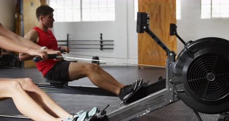 contra : Side view of an athletic Caucasian woman and man wearing sports clothes cross training at a gym, sitting side by side and exercising on rowing machines, in slow motion Stock Footage