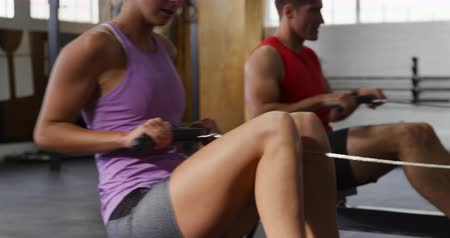 pull out : Side view of an athletic Caucasian woman and man wearing sports clothes cross training at a gym, sitting side by side and exercising on rowing machines, in slow motion Stock Footage