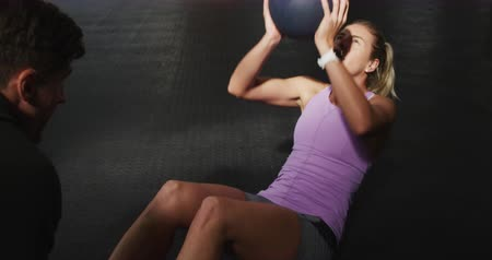 vychovávat : Front view of an athletic Caucasian woman wearing sports clothes holding a medicine ball, doing sit ups and raising teh ball above her head, with a mail trainer holding her feet, in slow motion Dostupné videozáznamy