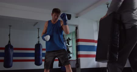 спортивная одежда : Front view of a Caucasian male kickboxer practicing a kick against a pad held by a bald Caucasian male trainer in a boxing gym, slow motion. Busy chefs at work in commercial kitchen.