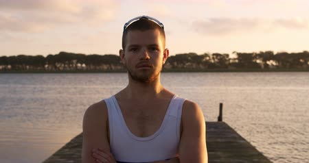 remo : Portrait of a Caucasian male rower standing on a jetty, looking at the camera, during a sunset, in slow motion