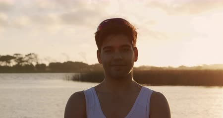 kürek çekme : Portrait of a Caucasian male rower standing on a jetty, looking at the camera and smiling, during a sunset, in slow motion Stok Video
