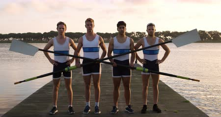 Front view of four Caucasian male rowers, standing in a row on a jetty, holding oars, during a sunset, in slow motion