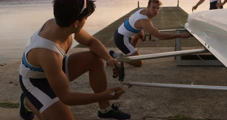 remo : Side view of two Caucasian male rowers kneeling by a boat on a jetty, preparing the boat before a practice, with their teammate standing behind the boat, during a sunset, in slow motion