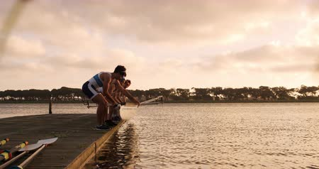 négy : Side view of four Caucasian male rowers, standing in a row on a jetty, holding a boat, landing it on the water, during a sunset, in slow motion Stock mozgókép