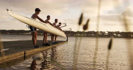 remo : Side view of four Caucasian male rowers, standing in a row on a jetty, holding a boat, taking it out of the water, holding it above their heads bottom up, during a sunset, in slow motion Filmati Stock