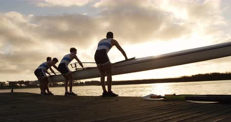 kürek çekme : Rear view of four Caucasian male rowers, standing in a row on a jetty, holding a boat, taking it out of the water, holding it above their heads bottom up, during a sunset, in slow motion Stok Video