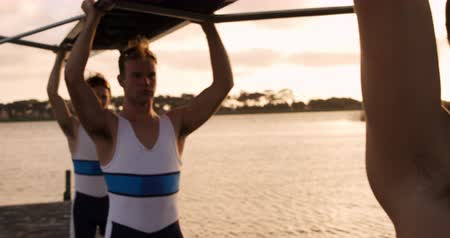 kürek çekme : Front view close up of four Caucasian male rowers, standing in a row on a jetty, holding a boat, taking it out of the water, holding it above their heads bottom up, during a sunset, in slow motion Stok Video