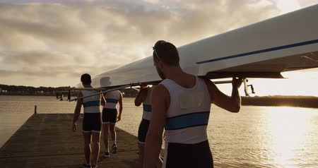 Rear view of four Caucasian male rowers, standing in a row on a jetty, holding a boat on their shoulders, walking with it, during a sunset, in slow motion