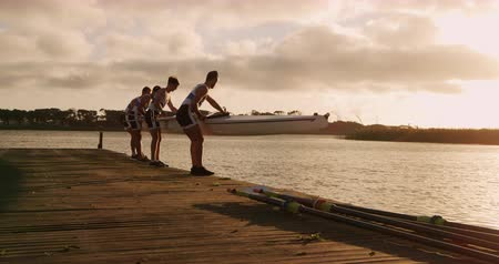 kürek çekme : Rear view of four Caucasian male rowers, standing in a row on a jetty, holding a boat, landing it on the water, during a sunset, in slow motion Stok Video